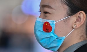 An airport worker wears a face mask with a sticker of the Chinese flag at Tianhe airport in Wuhan