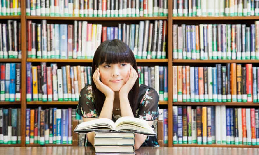 Woman daydreaming in a library