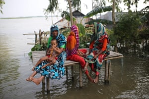 Kurigram, Bangladesh. People sit on a bamboo platform surrounded by flood waters after torrential monsoon rains swept away homes and triggered landslides across south Asia
