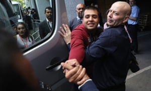 Jan Ghazi, (out of shot) greets his brother Haris who outside a Home Office processing centre in Croydon, south London.