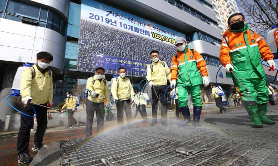 South Korean government officials spray disinfectant in front of the Daegu branch of the Shincheonji Church of Jesus