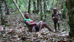 A Baka woman and her child rest in Messok Dja forest after a fishing expedition.