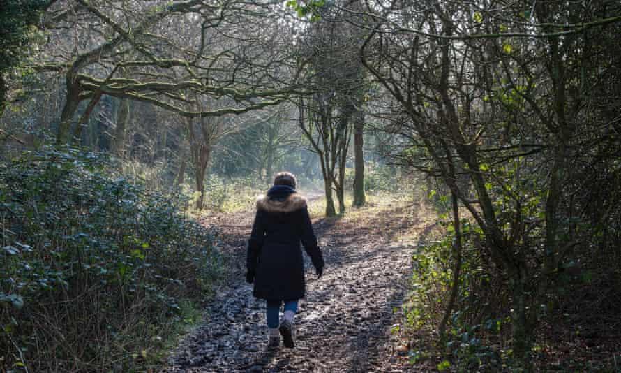 Woman walking through Kingley Vale woods
