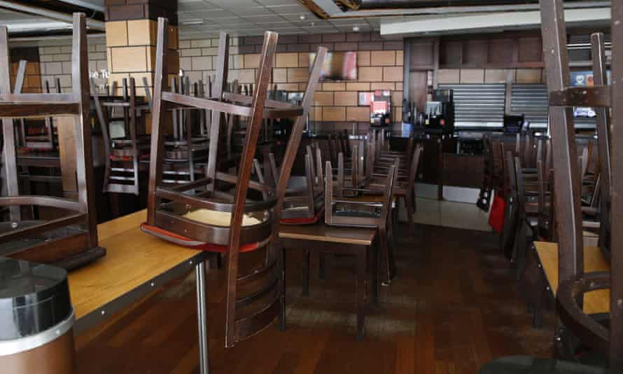 Chairs and tables stacked up in a deserted pub.