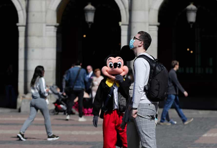A man in a face mask stands near a person in a Mickey Mouse costume in Plaza Mayor, Madrid