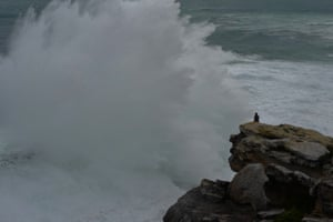 A young man photographs the wild weather using his mobile phone at Dee Why Head in North Curl Curl.