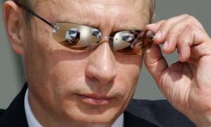 Russian president Vladimir Putin adjusts his sunglasses.