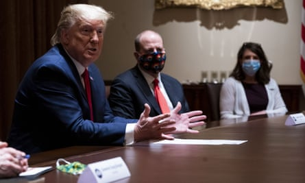 Donald Trump eschews a face mask in a cabinet meeting attended by the Colorado governor, Jared Polis, centre, last month.