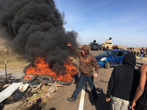 Dakota Access pipeline demonstrators stand next to burning tires as armed soldiers and law enforcement officers assemble to force them off private land where they had camped to block construction