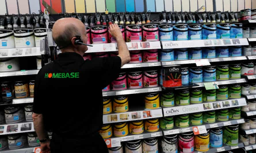 A Homebase sales assistant tidying a shelf of paints
