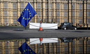 An EU flag left by anti-Brexit demonstrators is reflected in a puddle in front of the Houses of Parliament.