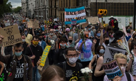 A large procession of Black Trans Lives Matter protesters holding various signs on a London street