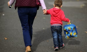Anonymous shot from behind of woman holding hand of young boy carrying lunchbox
