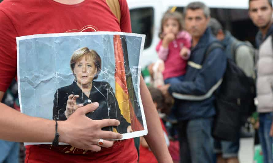 A refugee holding a picture of Merkel in September 2015 after the arrival of refugees at the main train station in Munich, southern Germany.