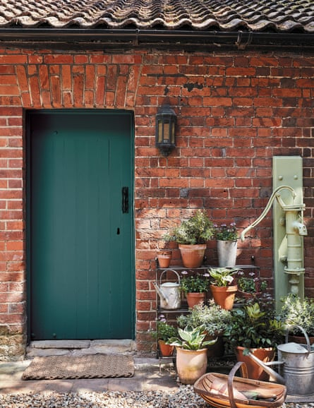 A dark green solid wooden front door in a bare brick country cottage with terracotta pots to one side