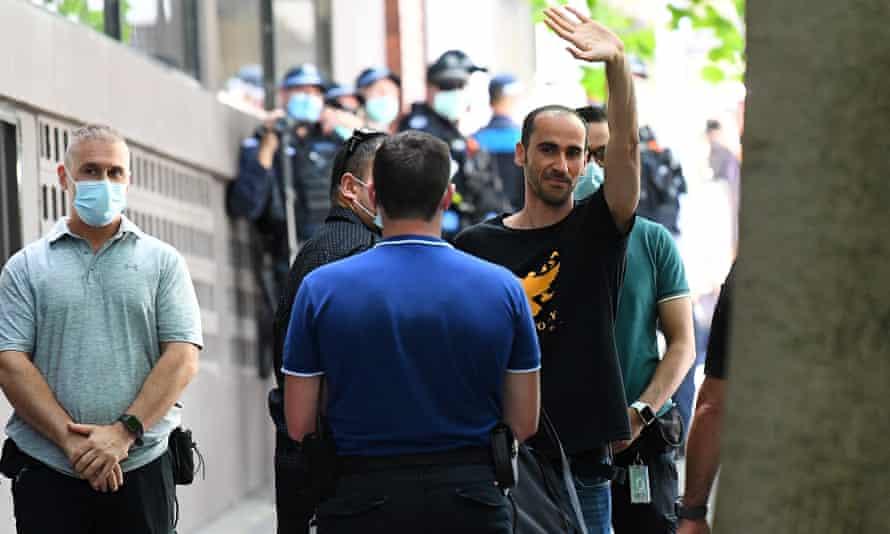 Mostafa Azimitabar waves as he leaves the Park Hotel in Carlton, Melbourne