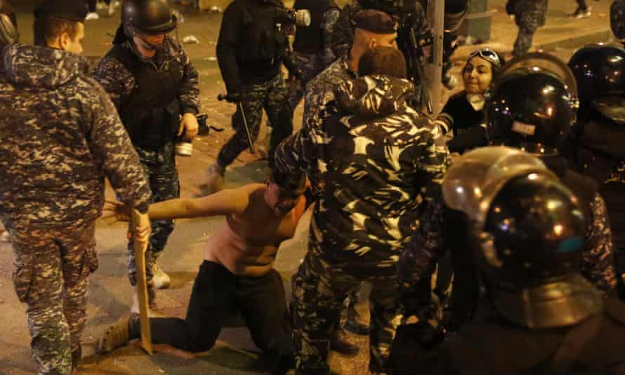 Riot police officers beat an anti-government protester near the parliament square, in downtown Beirut.