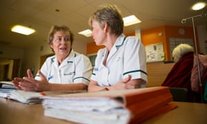 Two occupational therapists sat at a desk with case files