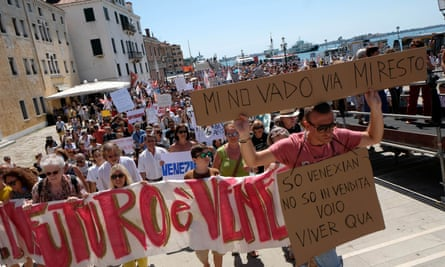 "A resident holds a placard saying, in Venetian dialect ""I'm not going, i'm staying"" during a protest in Venice last month."
