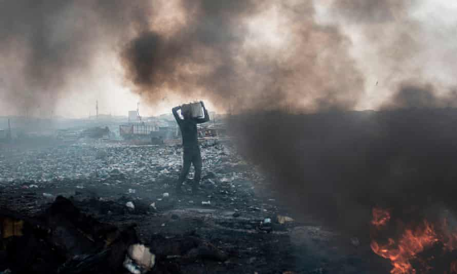 A man carries electronic waste at the Agbogbloshie dumpsite in Accra