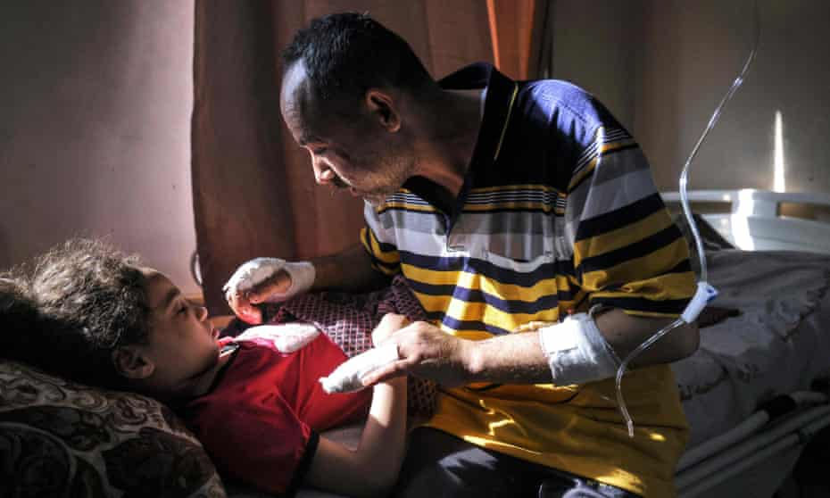 Palestinian Ryad Eshkuntana, checks his daughter Suzy, as they receive medical care at al-Shifa hospital, 19 May. His wife and other children were killed in an Israeli air strike.