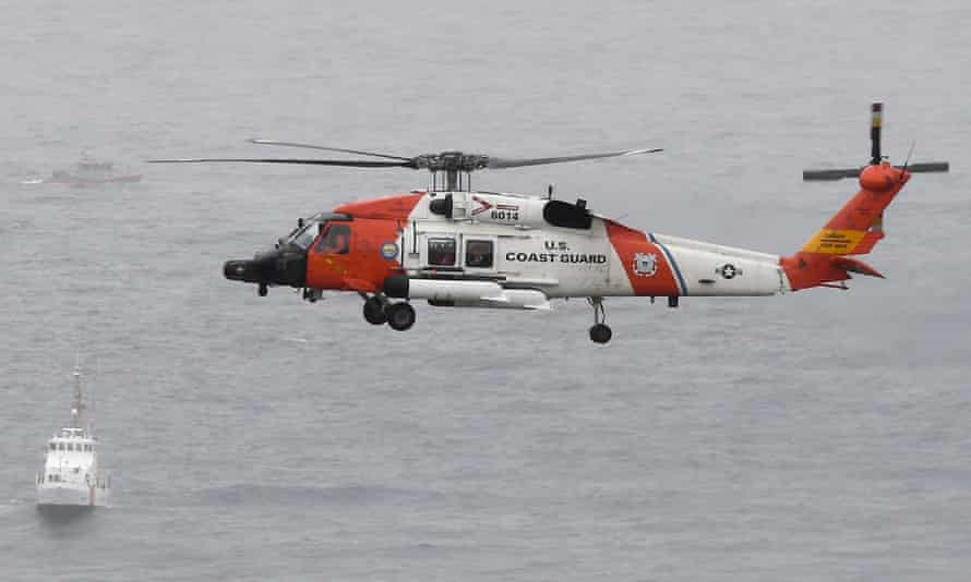 A US coast guard helicopter flies over the area where a boat capsized just off the San Diego coast.
