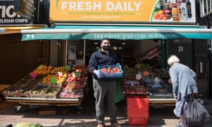 A greengrocer wears a mask as he organises his shop