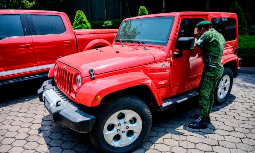 A soldier inspects a Jeep