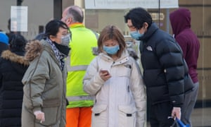 People wearing masks look at a mobile phone