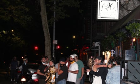 Customers have a drink in front of a bar on Saint-Mark Place in the East Village, New York, on 18 June.