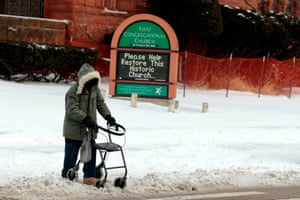 A person with a walker goes over snow as they cross Canfield Avenue in Detroit.