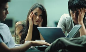 A man and woman looking sad and at a loss, gripping their heads with their laptops open