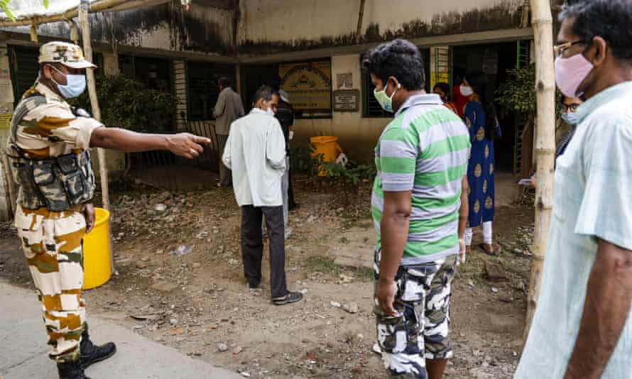 An Indian paramilitary asks masked voters to maintain physical distance outside a polling booth.