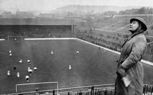 An air raid warden watches for enemy planes at a match between Charlton and Arsenal in London in 1940.
