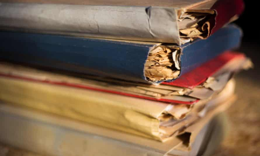 A stack of several old folders stuffed with papers.