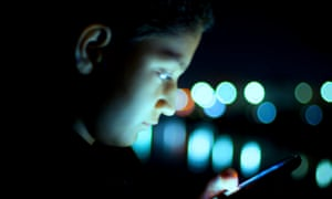 Boy busy using cell phone at night
