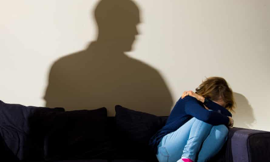 shadow of man standing over cowering woman