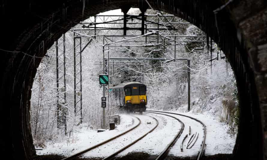A Scotrail train leaves the station in the snow in Cambuslang, Glasgow