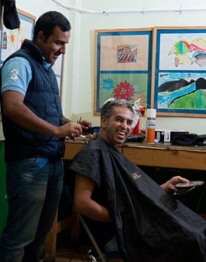 Neva cuts the hair of his fellow Iranian, Mehdi. Both have been granted refugee status.