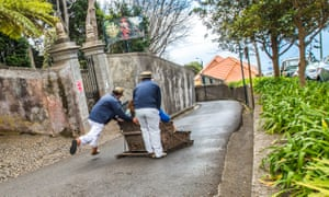 """A wicker toboggan ride through narrow streets, with two """"drivers"""" in traditional boaters guiding"""