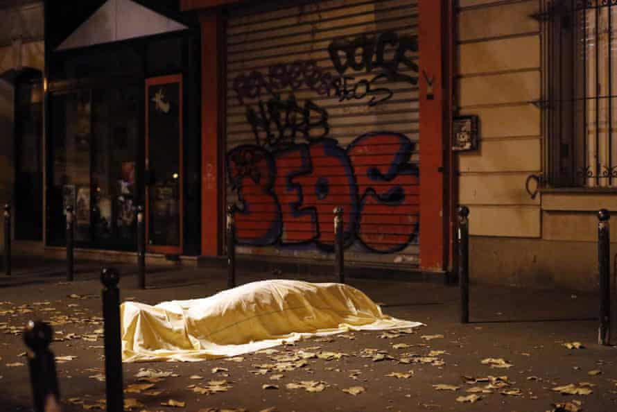 FILE - A victim of a terrorist attack lies dead outside the Bataclan theatre in Paris, Nov. 13, 2015. The Islamic State group claimed responsibility for Friday's attacks on a stadium, a concert hall and Paris cafes that left more than 120 people dead and over 350 wounded. (AP Photo/Jerome Delay, File)