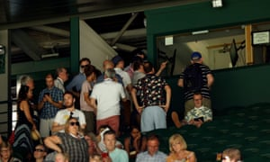 People crowd round a screen showing England's match against Sweden at Wimbledon