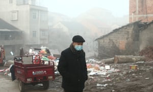An old man wearing a medical mask walks in the village at sunrise in Jianli county, Hubei province.