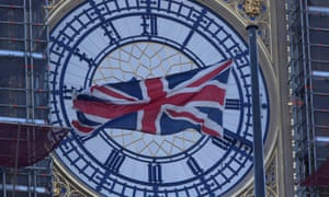 A union jack flag flying in front of Big Ben at Westminster.