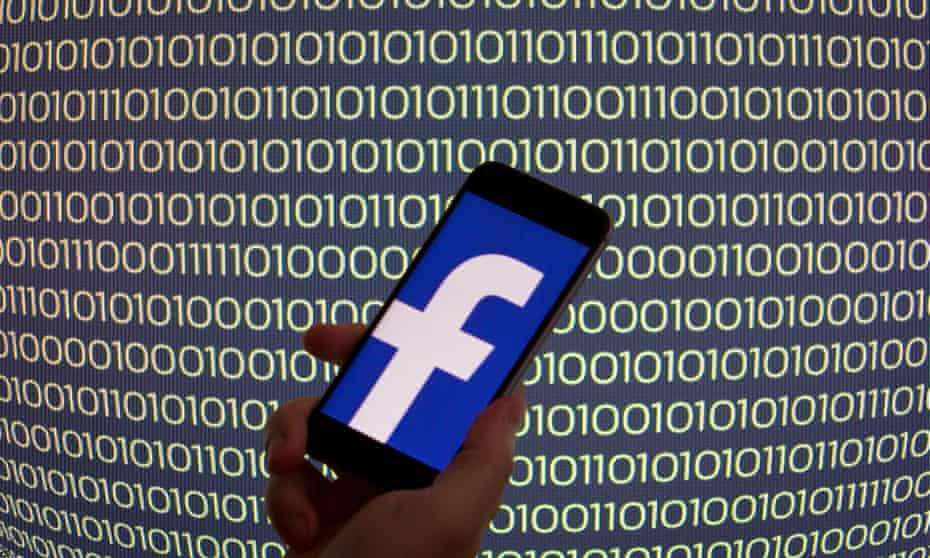 a facebook logo seen on a phone with a backdrop screen of binary code
