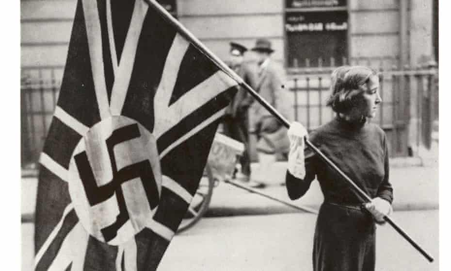 Female supporter of the British Union of Fascists carrying a flag in London in the 1930s.