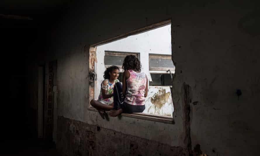 Two girls hang out inside Criança Feliz, an invaded office in Boa Vista, Brazil, that functions as a residence for Venezuelan migrants.