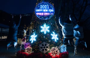 Young people celebrate in front of a 2021 tree at Namsan mountain in Seoul, South Korea
