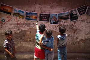 Children look at photos at an exhibition in Jabalia