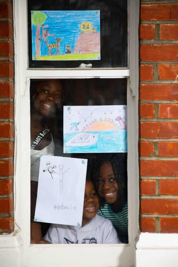 (Left to right) Shalomy, 10, Benjamin, six, and Stephanie, eight, display their animal artworks in a window